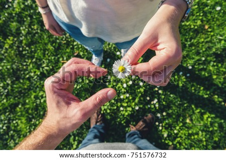 young couple in sneakers stands opposite on daisy Meadow and enjoying the love of nature, high angle footsie or flortrait, personal pespective from above. #751576732