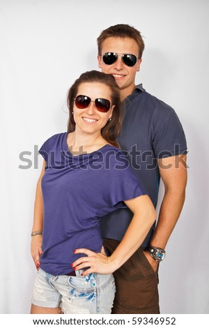 Young couple in sunglasses isolated on light background