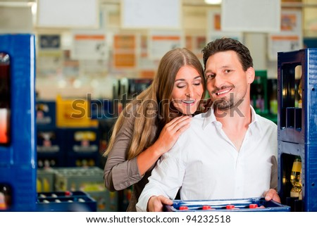 Young couple in supermarket buying beverages together