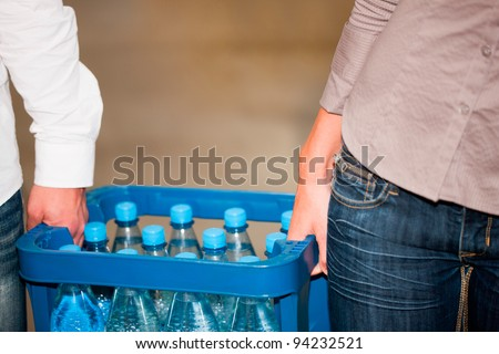Young couple in supermarket buying beverages together, close-up on box