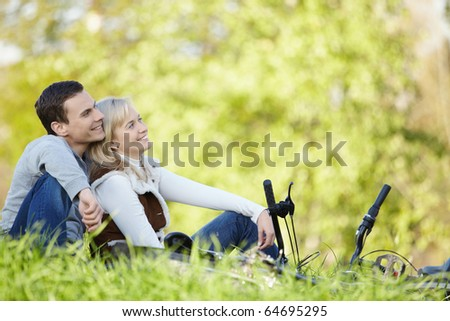 Young couple in the background of the autumn trees with bicycles