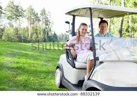 Young couple in the car for golf