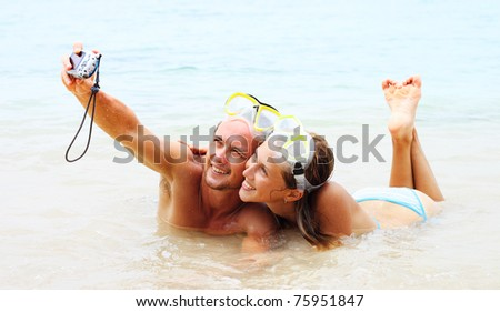 Young couple in the masks making photo of themselves in the sea