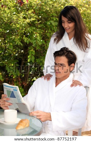 Young couple in the morning wearing bathrobe on a terrace