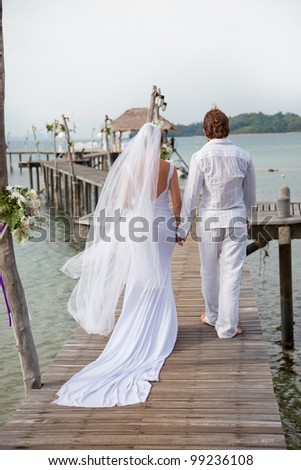 young couple in wedding dress walking along the pier