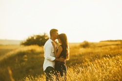 Young couple inlove on a field at sunset. Man kisinig woman on  forehead.