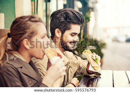 Shutterstock Young couple is eating sandwiches and enjoying.