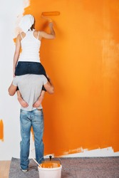 Young couple is having fun painting a wall