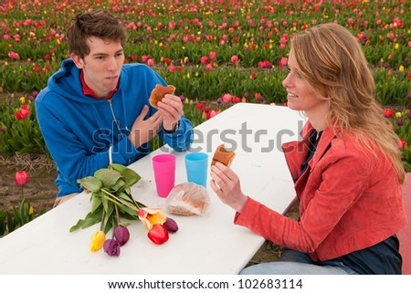 Young couple is having picnic in Dutch flower fields - stock photo