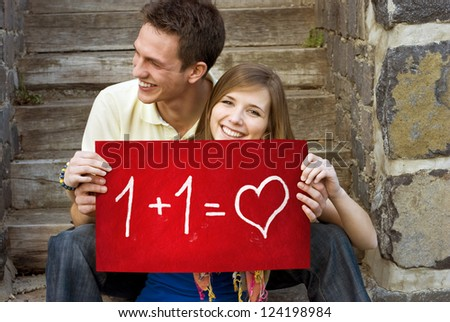 Young couple is holding board with romantic symbol.