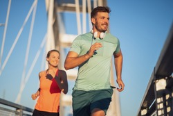 Young couple is jogging outdoor on bridge in the city.