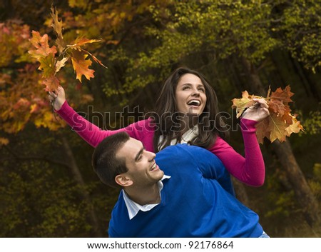 Young couple is playing piggyback in the autumn park