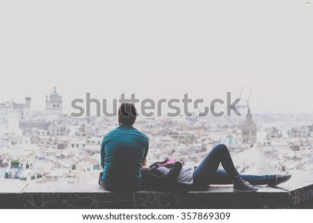 Young couple is relaxing and enjoying the view of the city. Toned picture