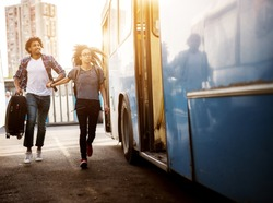 Young couple is rushing to catch a blue bus while holding each others hands.