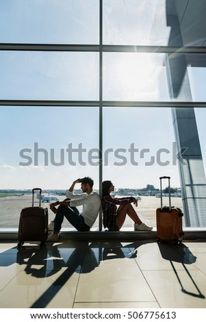 Young couple is sitting on windowsill at airport near luggage. They are looking forward pensively #506775613
