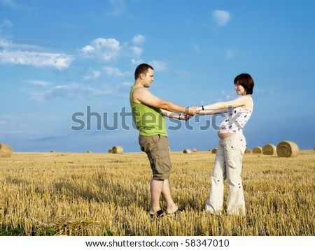 Young couple is staying in the meadow and hold on their hands. Woman is pregnant.