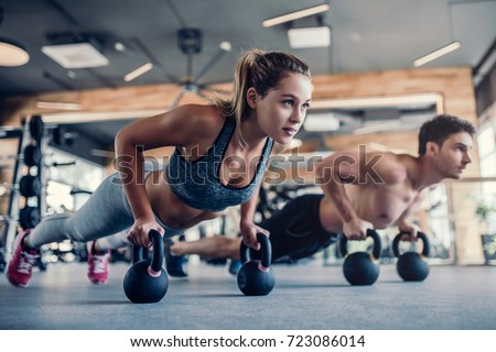 Young couple is working out at gym. Attractive woman and handsome muscular man are training in light modern gym. Doing plank on kettlebell. Push-up on weights.