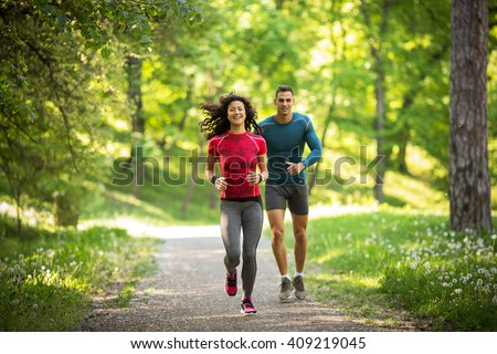 Young couple jogging at the woods.Green environment. #409219045