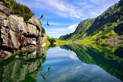 Young couple jump together into lake in mountains with beautiful blue water and reflexion.