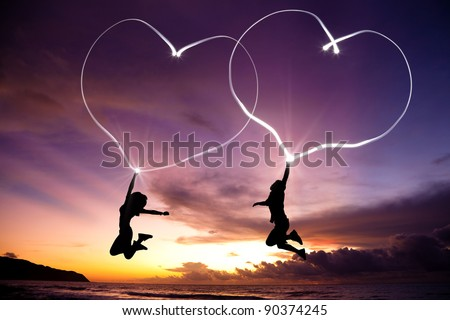 young couple jumping and drawing connected hearts by flashlight in the air on the beach before sunrise