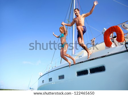 Young couple jumping in water from yacht #122465650