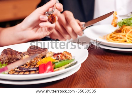 Young couple (just hands to be seen) enjoying dinner, he has some noodles while she is eating a good steak
