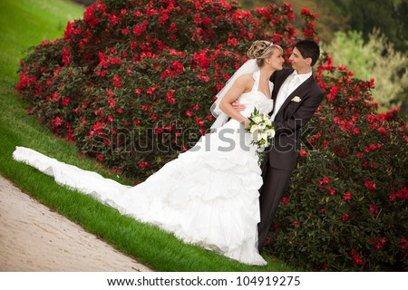 Young couple just married. groom and pretty bride are looking to each other after the wedding ceremony. she is blond and wearing a nice diadem. background red roses and foreground yellow bouquet roses