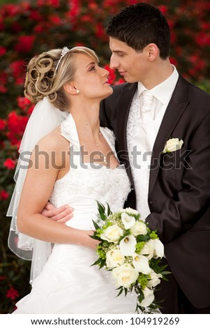 Young couple just married. groom wants to kiss his pretty bride after the wedding ceremony. she is blond and wearing a nice diadem. background red roses and foreground yellow bouquet roses