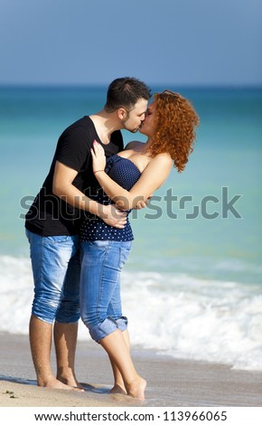 Young couple kissing at the beach.