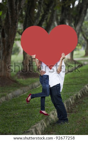 Young couple kissing behind red heart cutout in the nature