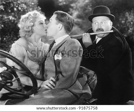 Young couple kissing each other affectionately while a man is playing flute