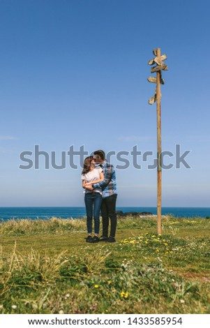 Young couple kissing embraced by a direction sign on the coast #1433585954