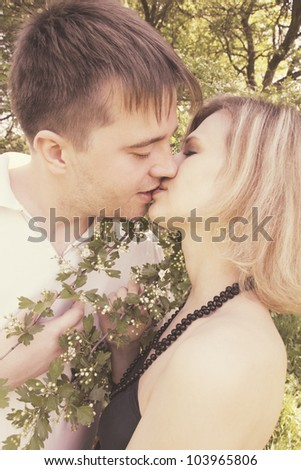 Young couple kissing near the blooming hawthorn