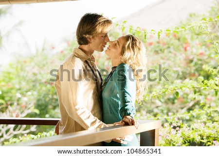 Young couple kissing on a tropical home's balcony overlooking a lush garden while on honeymoon.