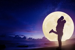 young couple kissing on beach and watching the moon.Celebrate Mid autumn festival
