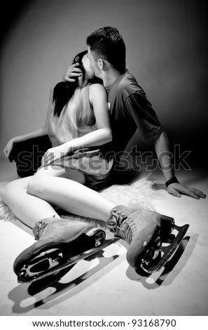 Young couple kissing on floor.Woman wearing ice skating boots