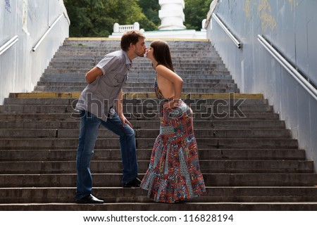 Young couple kissing on stairs in a tunnel