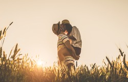 Young couple kissing on the background of a sunset in the wheat field
