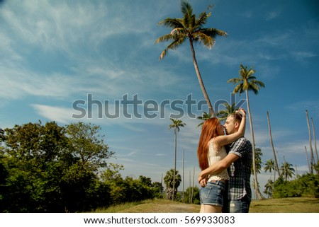 young couple kissing on the background of palm trees #569933083