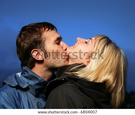 Young couple kissing outdoors at dusk.