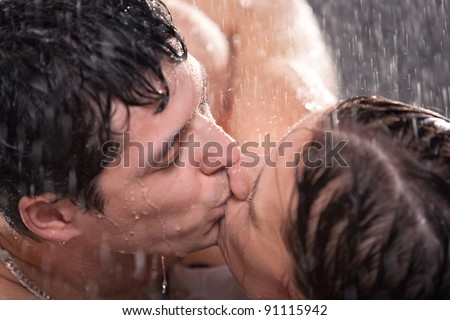 Young couple kissing portrait. Water studio photo.