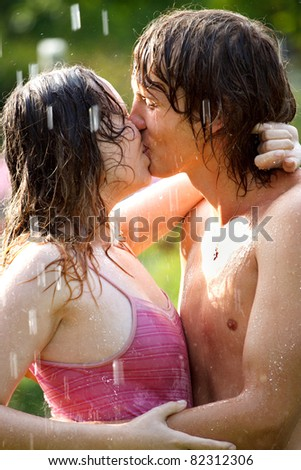 Young couple kissing under the rain