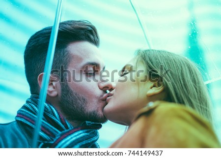 Young couple kissing under transparent umbrella - Girlfriend and boyfriend having tender moments - Tender moments and love concept - Focus on man eye - Radial blue and green filters editing #744149437