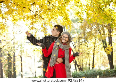 young couple laughing and enjoying in autumn, leaves falling on them