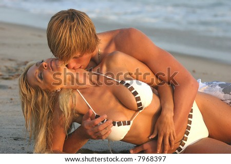 Young couple laying on their sides at the beach embracing with the Man from behind