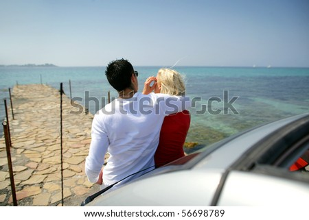 Young couple leaning on a car face to the sea