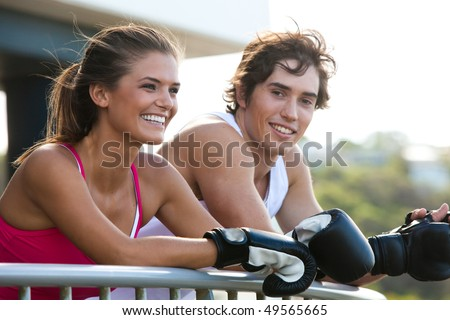 Young couple leaning over a railing in an outdoor setting. They are both wearing boxing gloves and smiling. Horizontal shot.