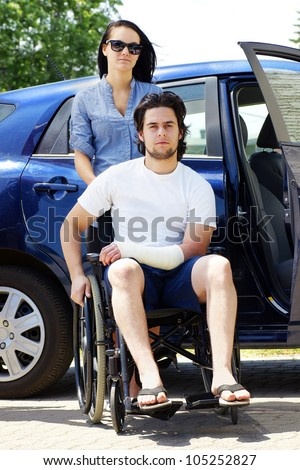 Young couple leaving or arriving to the hospital,young man in wheelchair with a cast on his hand.