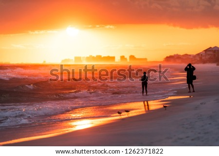Young couple looking at dramatic orange red sunset in Santa Rosa Beach, Florida with Pensacola coastline coast skyline in panhandle with ocean gulf mexico waves