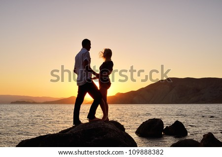 Young couple looking at each other, holding hands on beach